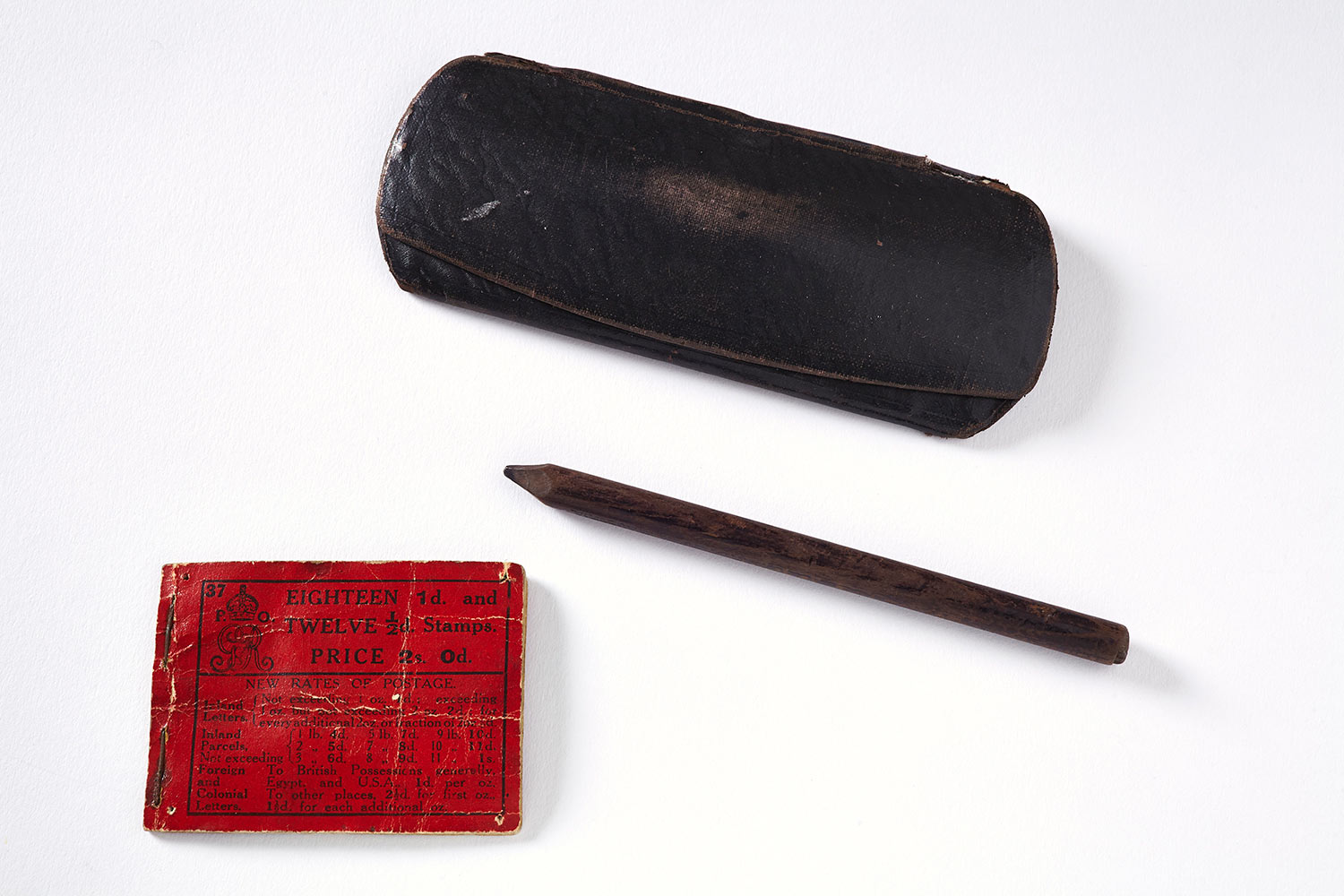 Contents of Tom Clarke's Pocket, a pencil, a book of stamps and a glasses case