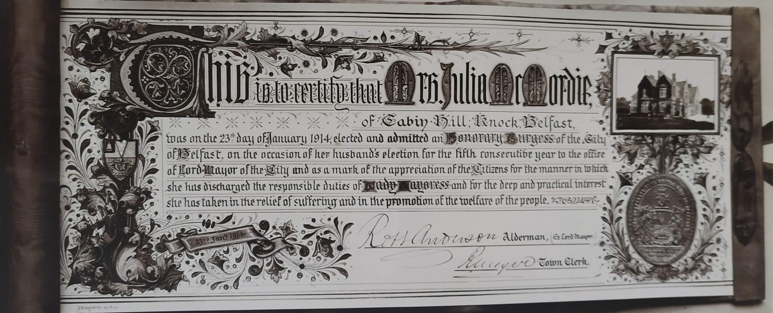Photograph of scroll presented to Mrs. Julia McMordie admitting her as an Honorary Burgess of the City of Belfast. 1914.